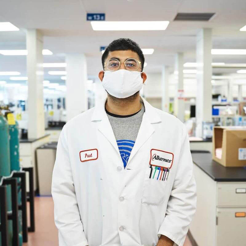 Man standing in lab coat with mask on in laboratory area at Alkermes.