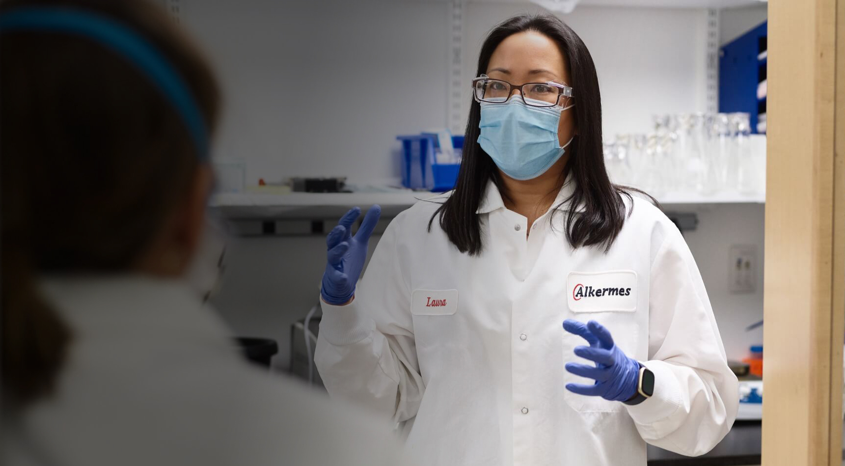 Woman in lab coat with blue gloves, glasses and a mask speaking to colleague at Alkermes