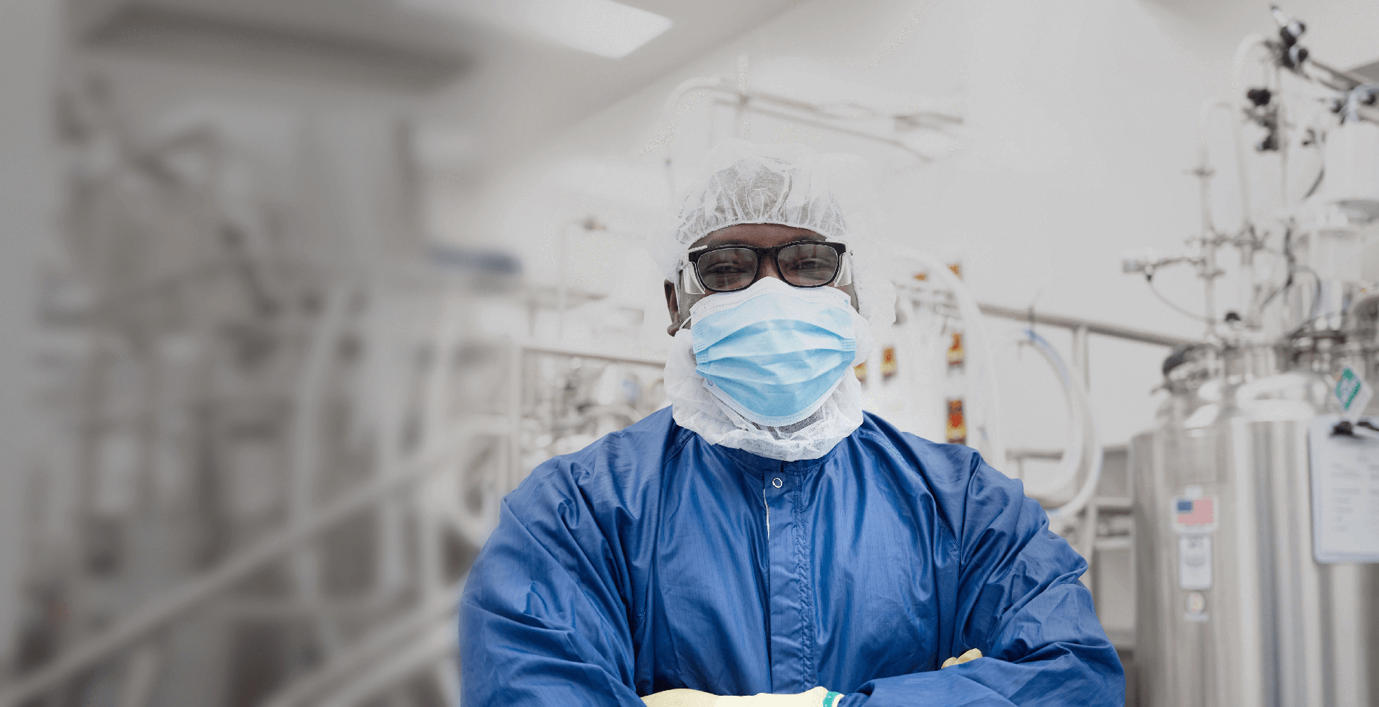 Man with glasses wearing mask and scrubs in manufacturing area at Alkermes.